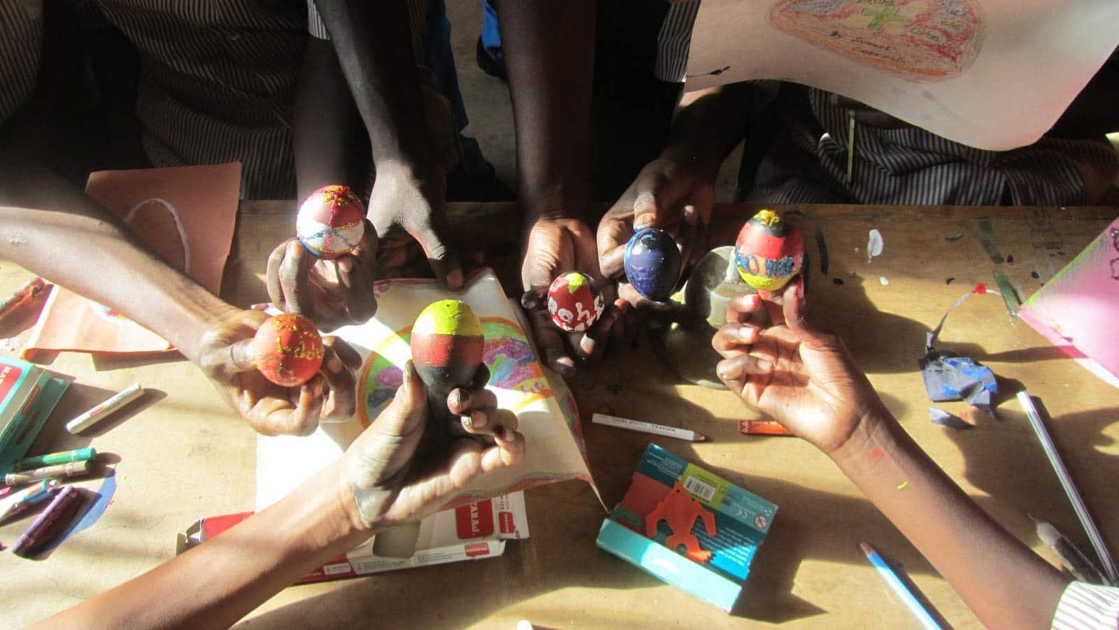 Mehrere Hände bemalen Ostereier im Freiwilligendienst