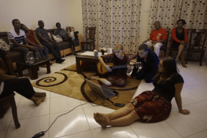 Menschen sitzen im Kreise zusammen und musizieren
