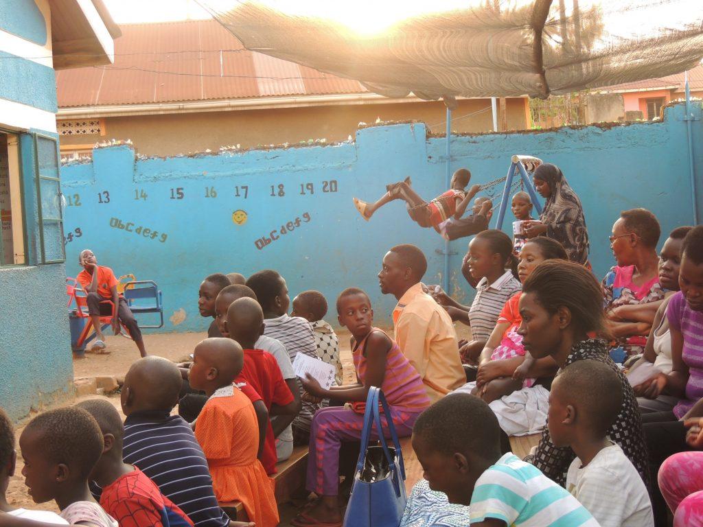 Eltern und Kinder bei einer Vorführung der Schüler:innen im Hof vom Children's Centre