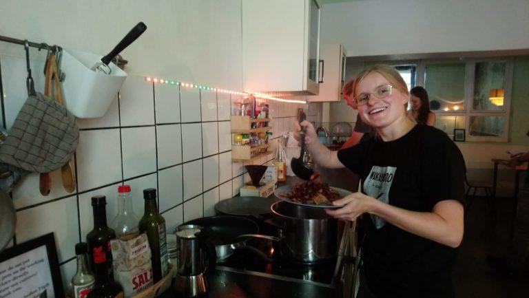 Jenny hält einen Kochlöffel über einem großen Topf mit Bohnen und lacht in die Kamera