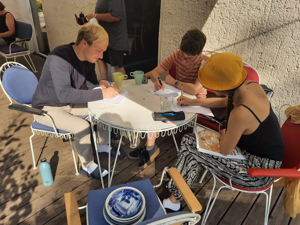 Nils, Jana und Lara sitzen an einem Tisch auf der Terrasse und unterschreiben Verträge.