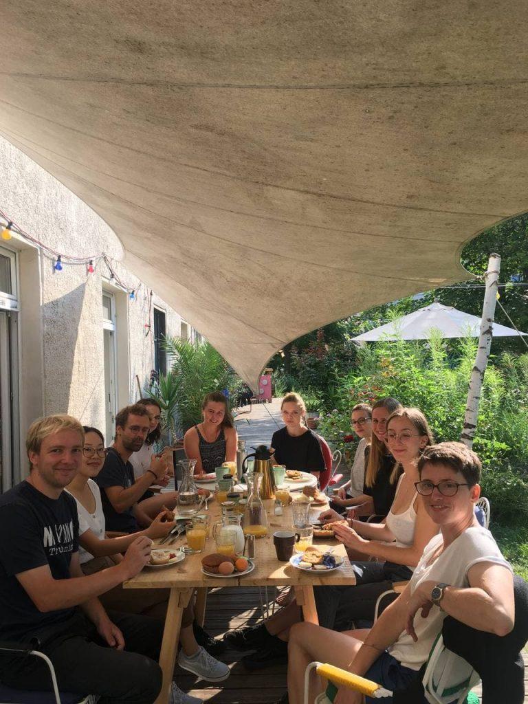 Mehrere junge Menschen sitzen an einem Tisch auf einer Terrasse beim Frühstück und lachen in die Kamera.