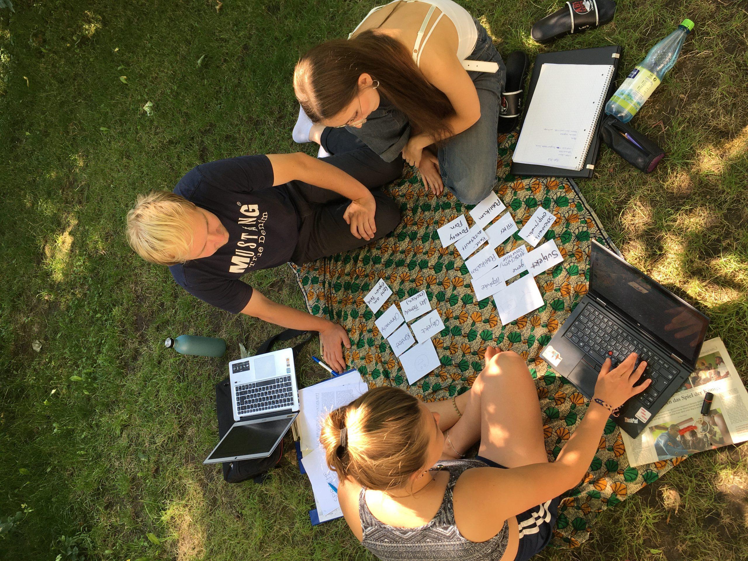 Nils, Lara und Lexi sitzen auf einer Decke im Gras mit ihren Laptops und haben Karteikarten vor sich ausgebreitet.